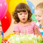 kids celebrating birthday party and blowing candles on cake